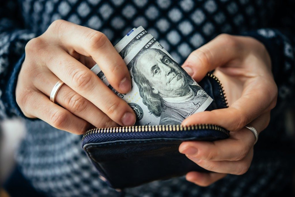 Person inserting money on her wallet