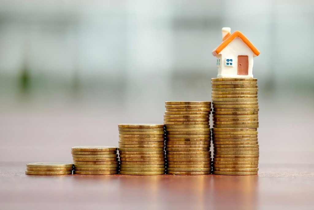 stack of coins getting taller with a miniature house on top of the talles stack