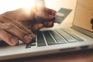 Holding credit car typng laptop