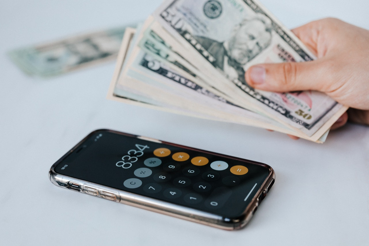 person using calculator with cash